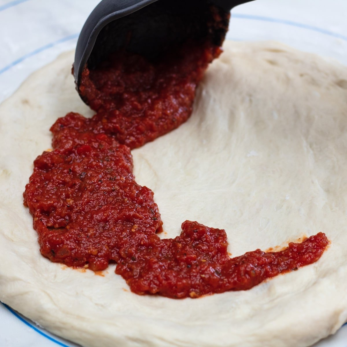 Cooked and blended pizza sauce being applied to pizza dough.
