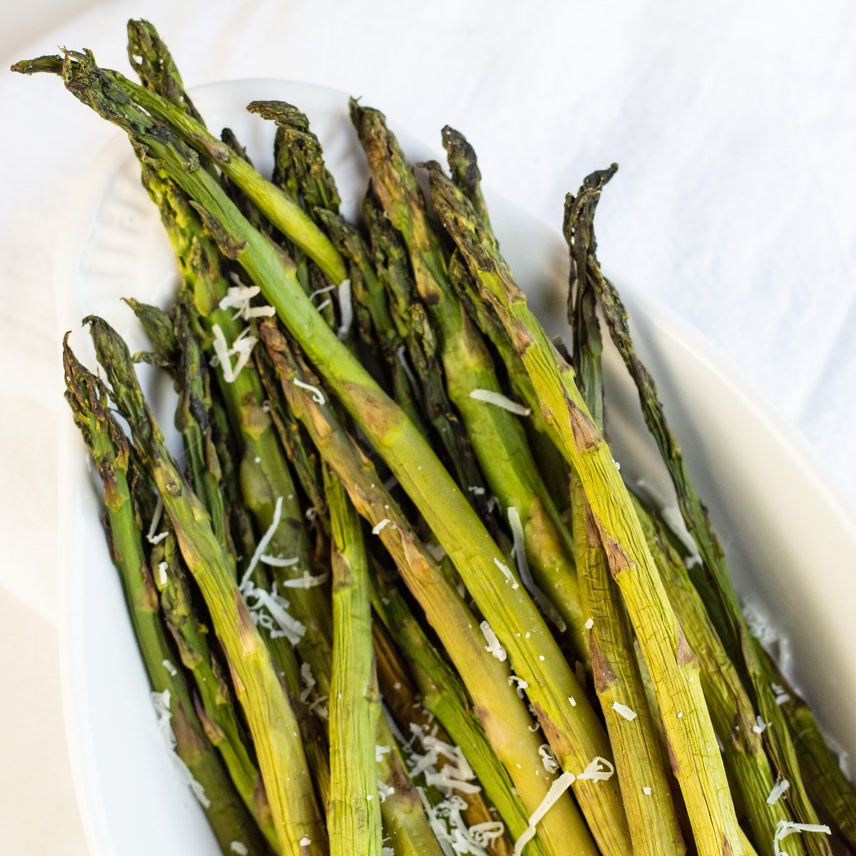 Smoked asparagus with freshly grated parmesan cheese on light background.