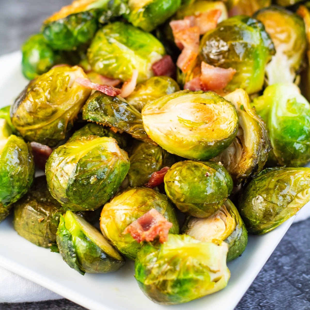 Hearty smoked brussel sprouts tossed in batter with bacon and served on white platter.