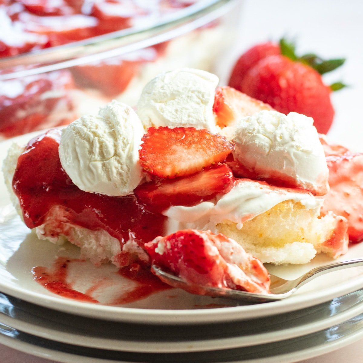 Strawberry angel food lush served on white plate with whipped cream and berries in background.