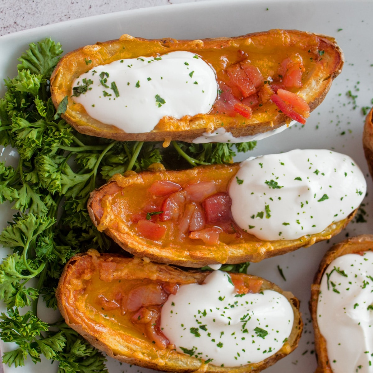 Three potato skins with sour cream and bacon on a white plate.