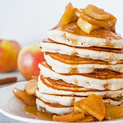 Apple cider pancakes, stacked on a white plate topped with baked apples and syrup.