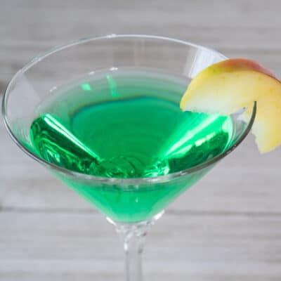 Appletini cocktail with sliced apple garnish.