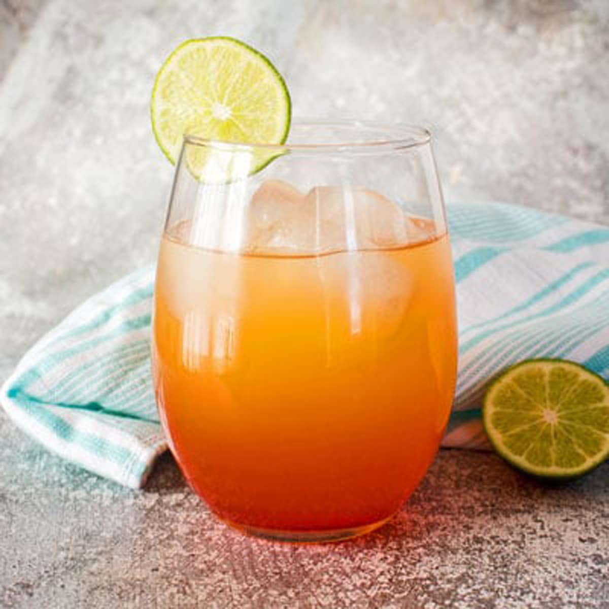 Jamaican rum punch in a glass with ice and lime slice.