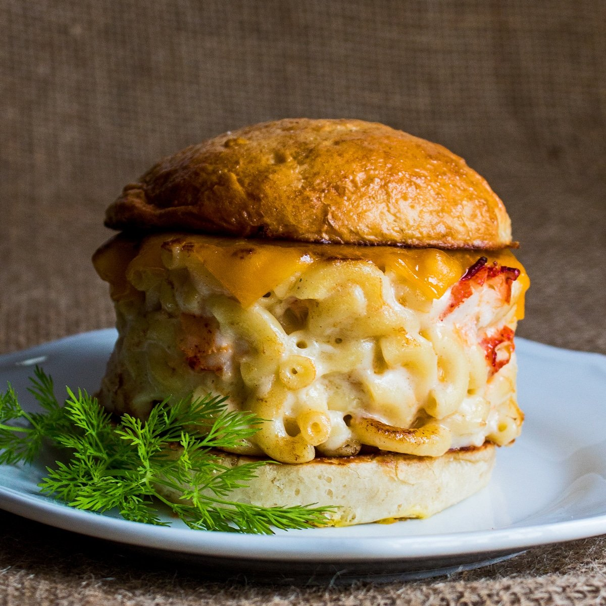 Lobster mac and cheese burger served on brioche bun.