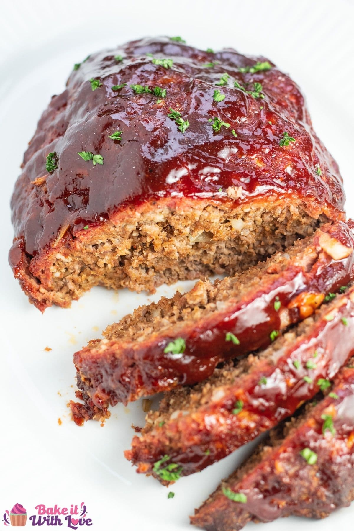 Tall overhead of the sliced smoked meatloaf on white platter.