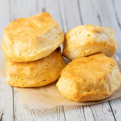 Air fryer biscuits cooked until golden and stacked on parchment paper.