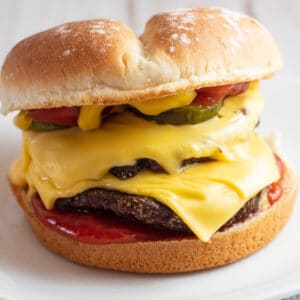 Air fryer frozen burger on bun with cheese and condiments.
