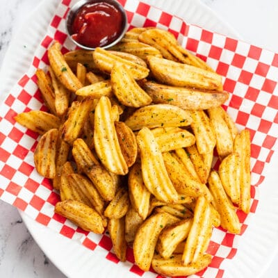 Air fryer frozen potato wedges served in picnic basket with ketchup.
