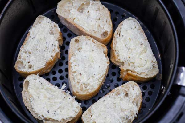 Process photo 4 of slices of bread with garlic spread in the air fryer basket.