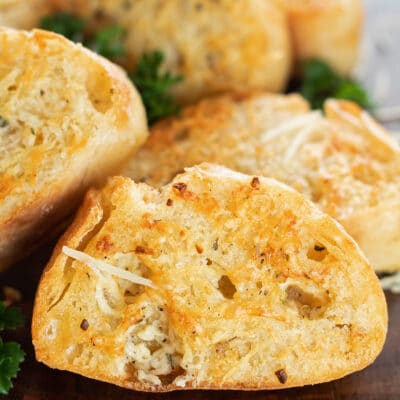 Perfectly toasted air fryer garlic bread slices on wooden cutting board.