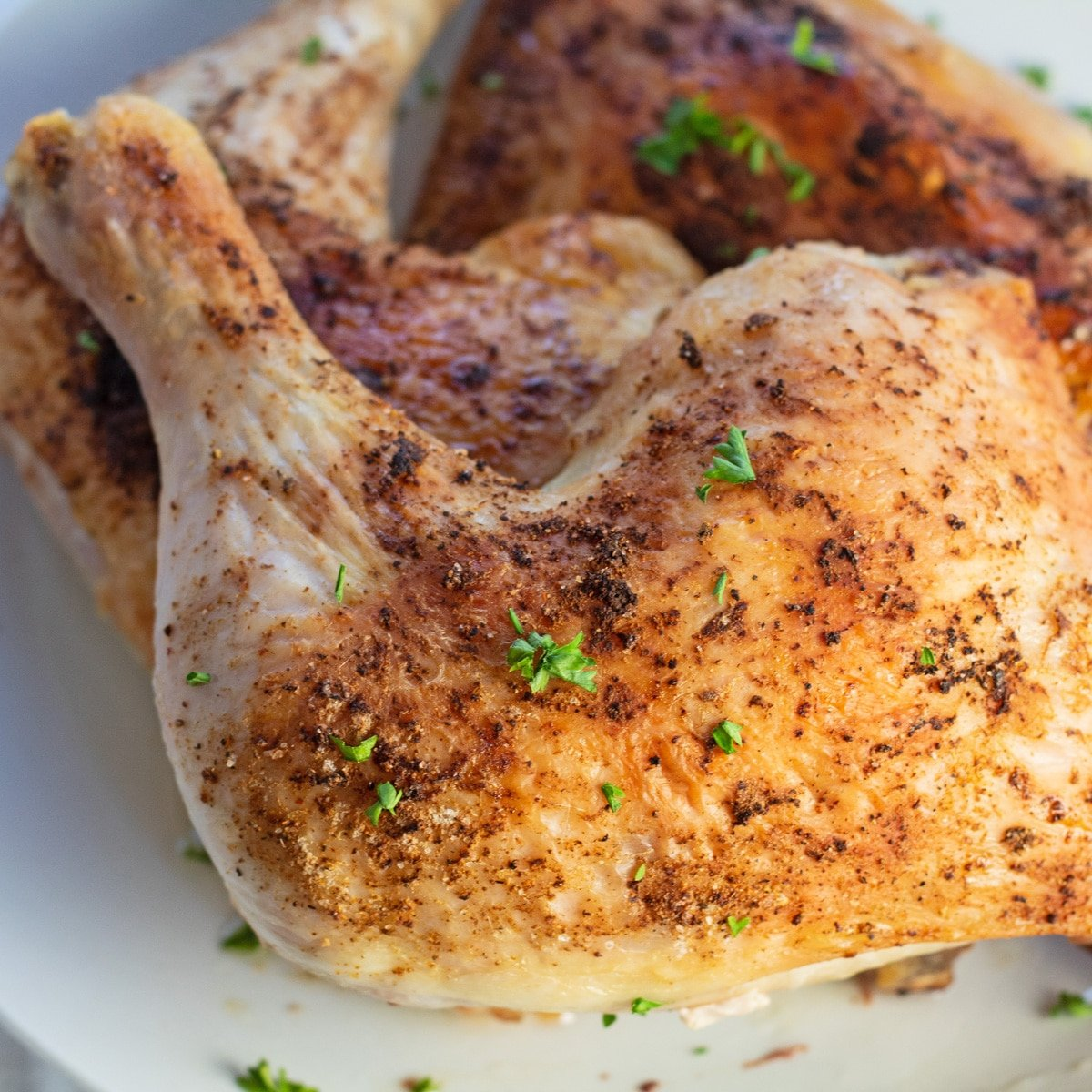 Baked chicken quarters garnished with parsley.