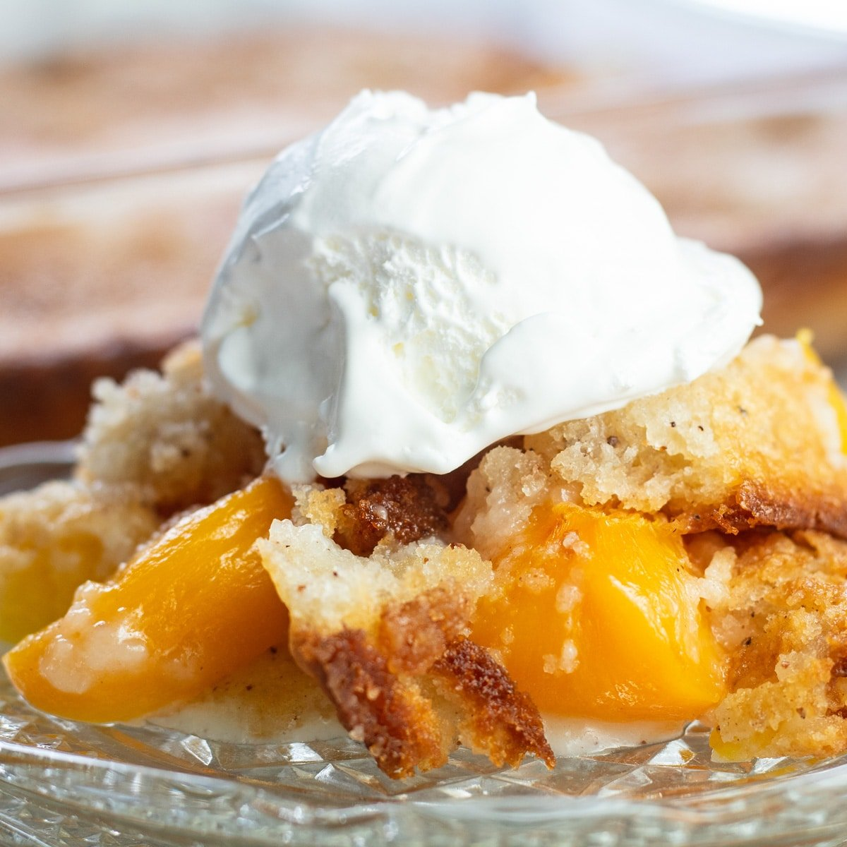 Bisquick peach cobbler served on glass plate with baking dish in background.