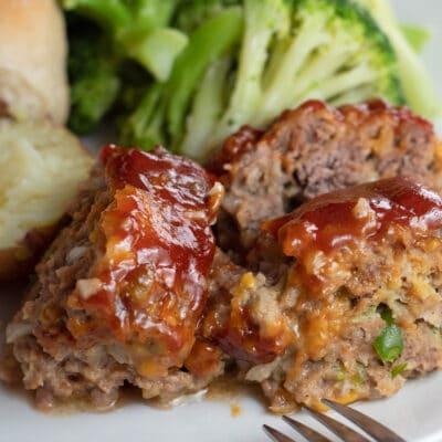 Primer cuadrado de las rebanadas de pastel de carne de barril de galleta servido en un plato blanco con patatas rojas y brócoli.