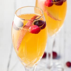 Mimosa mocktails in champagne flutes with sliced apple and cranberry garnish.