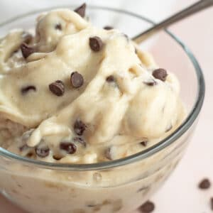 Mint chocolate chip nice cream in clear bowl topped with mini chocolate chip morsels.