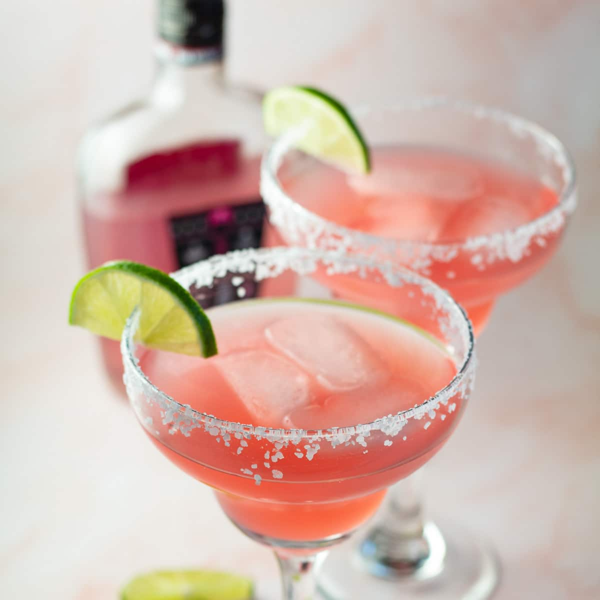 Pink vodka margarita serve din margarita glasses with lemon slice on rim.