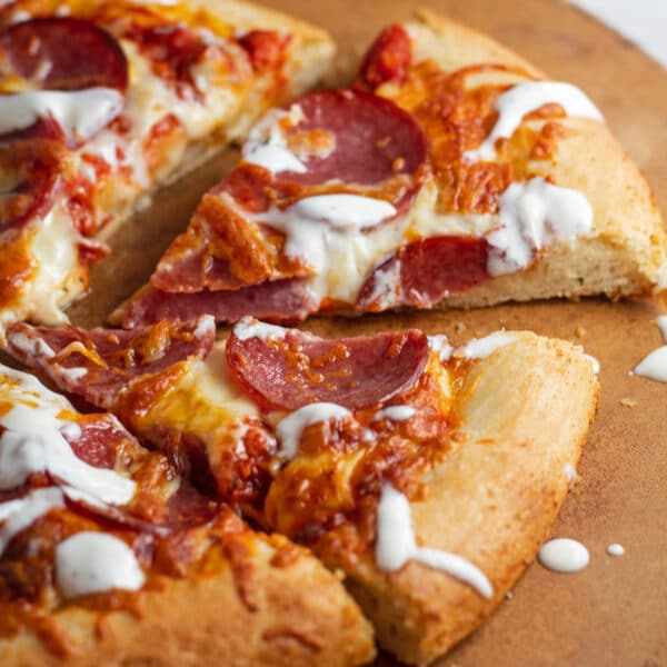 Sliced pizza drizzled with pizza aioli.