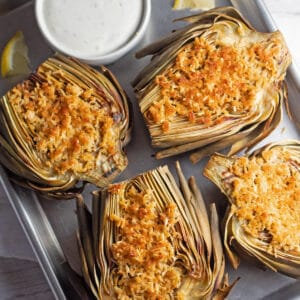 Roasted artichokes on a metal tray.