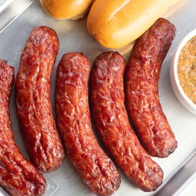 Square overhead of the smoked italian sausage on metal tray with buns and coarse mustard on sides.