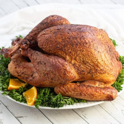 Traeger smoked turkey served on white platter with parsley and orange slices as garnish.