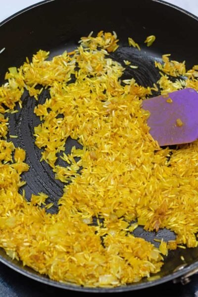 Process photo 5 of the rice and turmeric combined with sauteed onion and garlic.