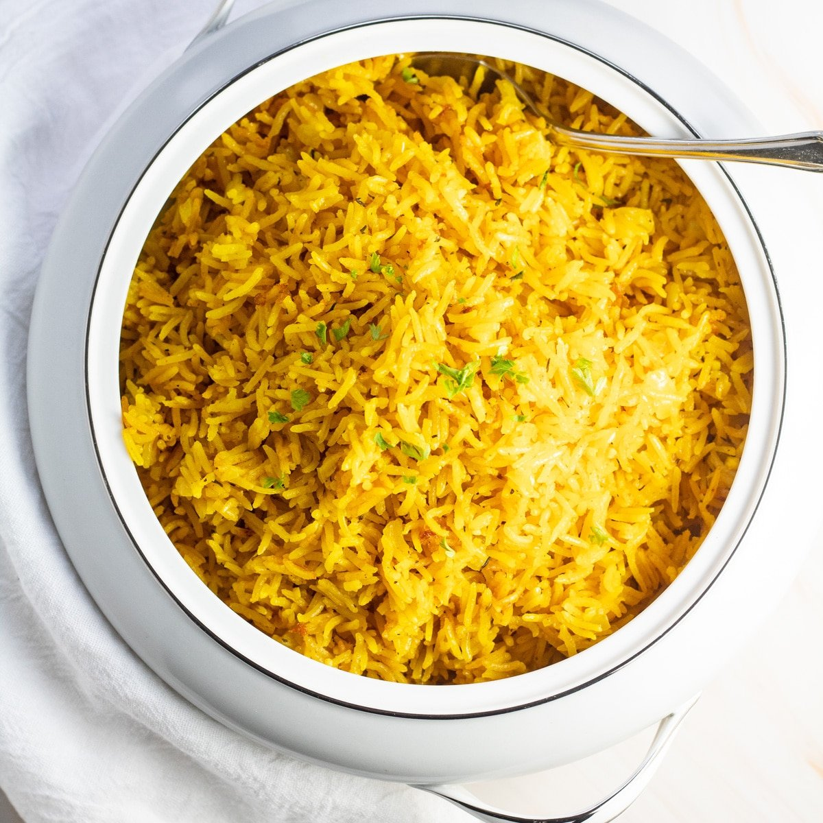 Turmeric rice in serving dish on light background.