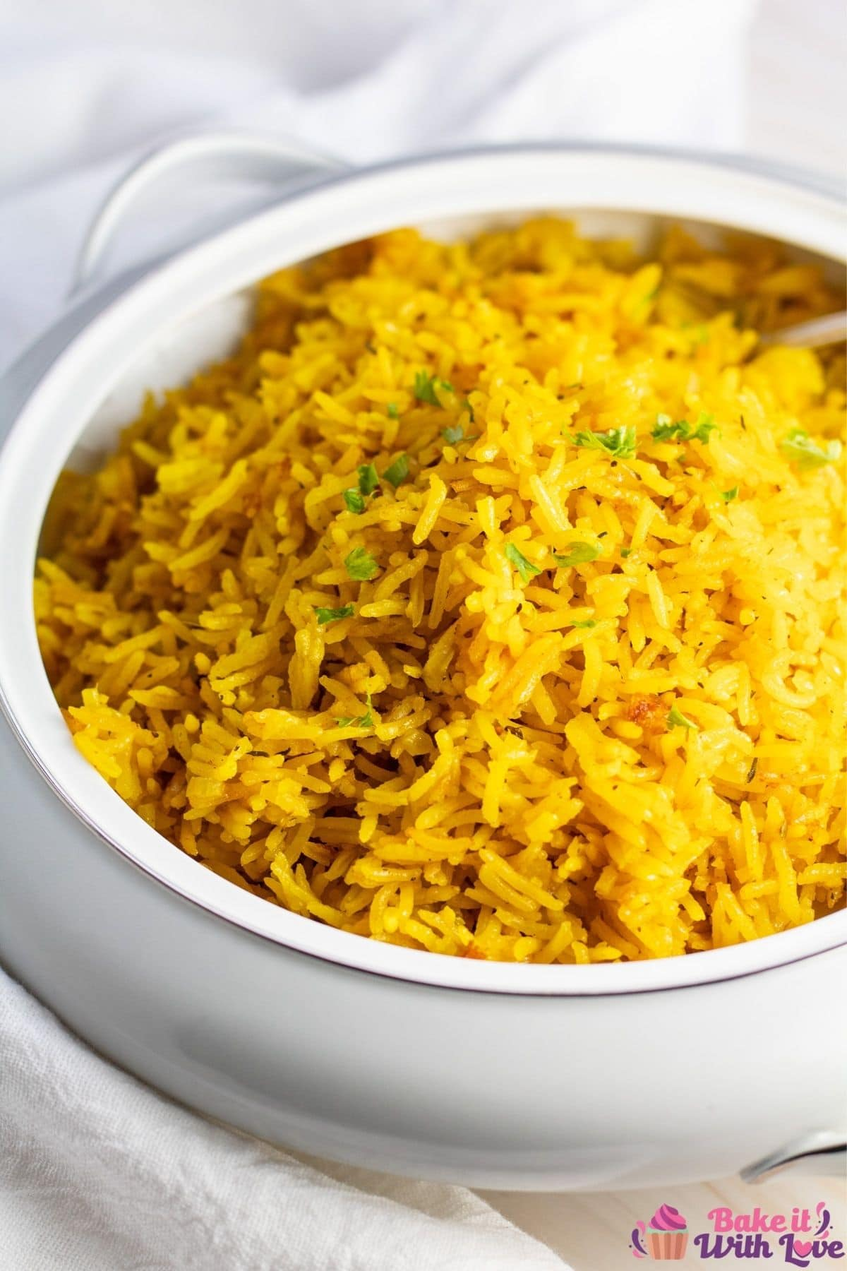 Tall image of the turmeric rice in serving dish.