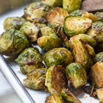 Balsamic roasted brussel sprouts on sheet pan with wooden spatula.