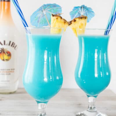 Frozen blue hawaiian cocktail served in hurrican glasses with pineapple garnish.