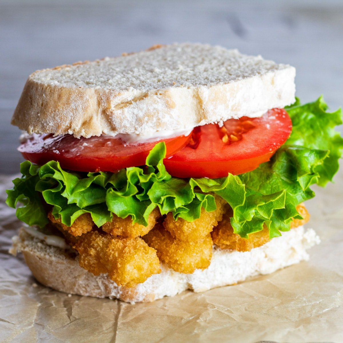 Fish stick sandwich with lettuce and tomato, on a plain background.