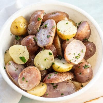 Boiled potatoes in a white bowl with parsley on top.