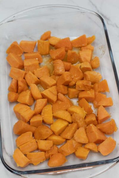 Process photo 1 of spreading the drained canned yams in baking dish.