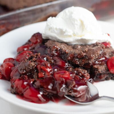 Chocolate cherry dump cake served with whipped cream on top and a spoonful in front.