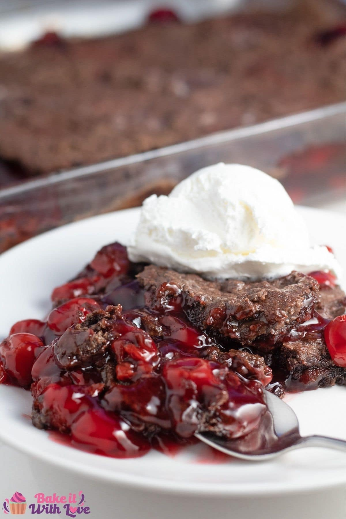 Tall image of the chocolate cherry dump cake served on plate with the baking dish in background.