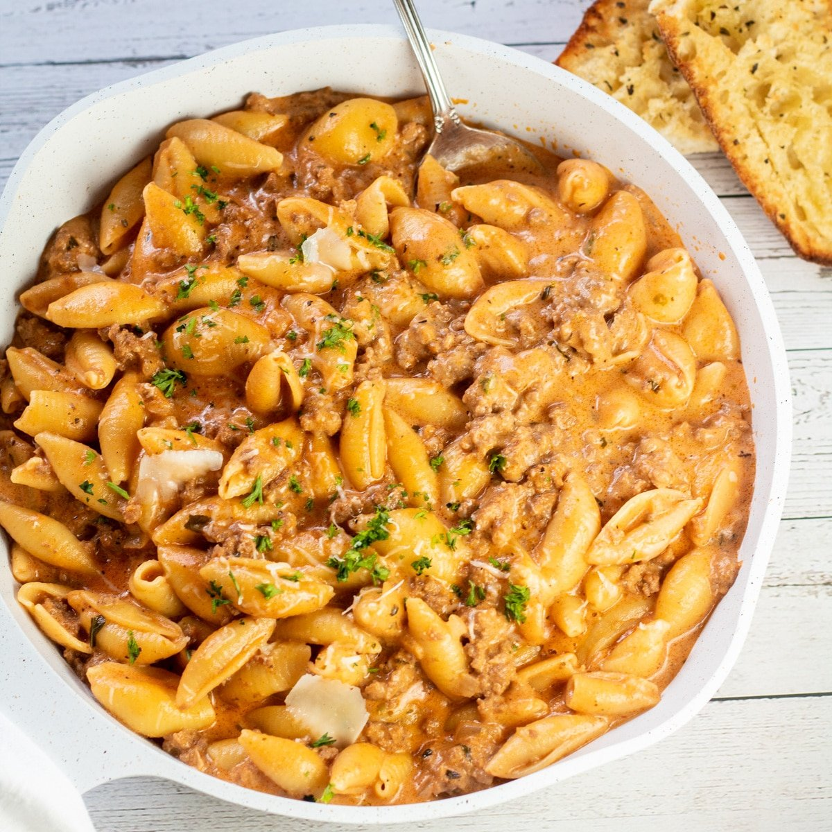 Creamy beef and shells with parsley garnish and garlic bread ready to serve.