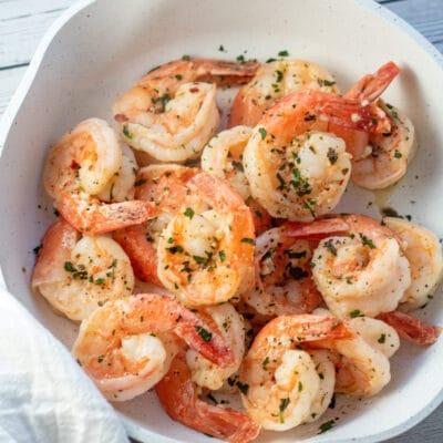 Garlic butter shrimp in skillet with parsley garnish.