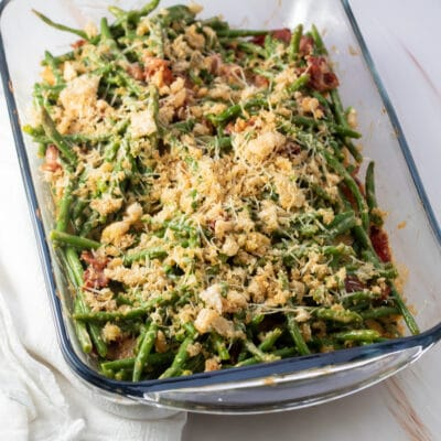 Green bean casserole with bacon in glass baking dish on light background.