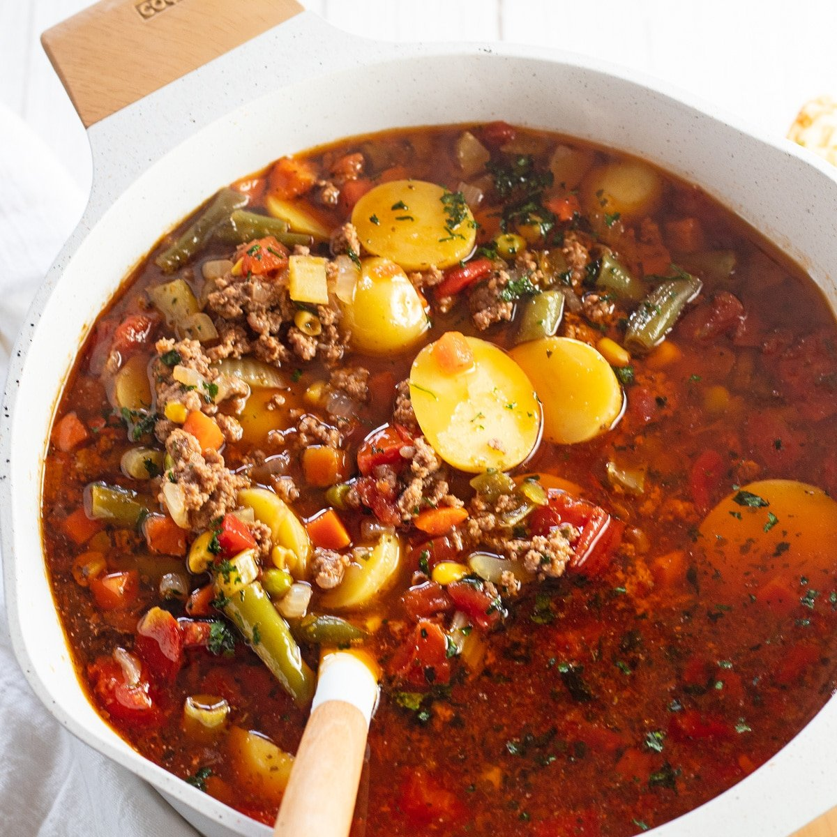 Hamburger soup in stock pot with white ladle rested on side.