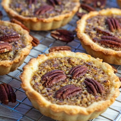 Pecan tartlets closeup on topping and pecans.