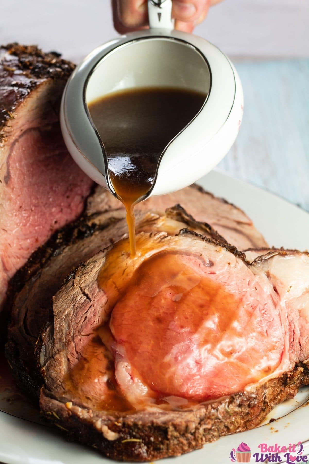Tall image of the prime rib au jus being poured over prime rib.