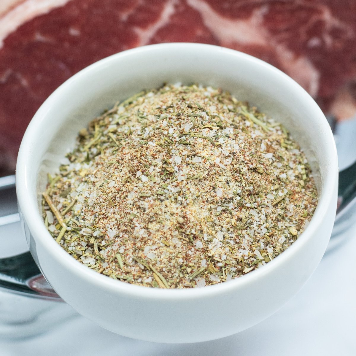 Prime rib rub combined in white bowl with prime rib in background.