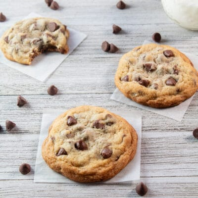 Small batch chocolate chip cookies on wooden grain background with scattered chips.
