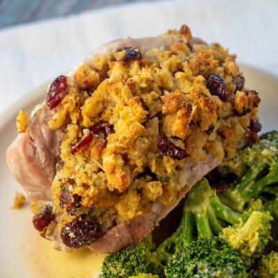 Stuffing stuffed pork chops on white plate with broccoli.
